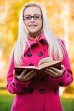Intelligente blonde Frau mit Buch Stockfoto