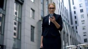 Intelligente Dame extrem glücklich, Geld auf, unter Verwendung des Smartphone online wetten zu gewinnen lizenzfreies stockfoto