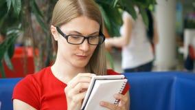 Intelligente dorstige student die in glazen in koffie het drinken kola van document kop zitten die in notitieboekje schrijven stock videobeelden