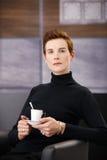 Intelligente Frau, die Kaffee im Lehnsessel trinkt Stockfotografie