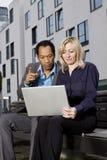 Intelligente Geschäftspaare, die draußen an Notizbuch arbeiten Stockbild