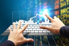 Intelligente Hand, die auf weißer Tastatur und hohem Diagramm schreibt Stockfotos