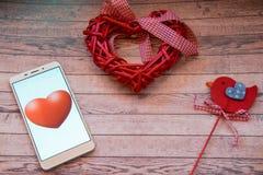 Intelligente Herzschläge Smartphone mit roten Herzen und rotem Vogel auf einem hölzernen blauen Hintergrund Valentinsgruß `s Them Stockfotografie