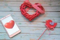 Intelligente Herzschläge Smartphone mit roten Herzen und rotem Vogel auf einem hölzernen blauen Hintergrund Valentinsgruß `s Them Lizenzfreie Stockbilder