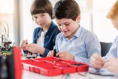 Intelligente junge männliche Kinder in der Werkstatt Lizenzfreie Stockbilder
