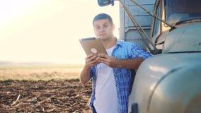 Intelligente Landwirtschaft Lebensstilmann-Landwirtfahrer steht mit einer digitalen Tablette nahe dem LKW Zeitlupevideo Porträt stock footage