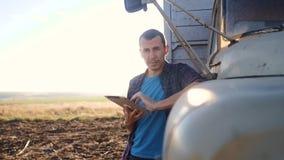 Intelligente Landwirtschaft Mannlandwirtfahrer steht mit einer digitalen Tablette nahe dem LKW Zeitlupevideo Porträtgeschäftsmann stock video footage