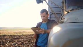 Intelligente Landwirtschaft Mannlandwirtfahrer steht mit einer digitalen Tablette nahe dem LKW Zeitlupevideo Porträtgeschäftsmann stock video