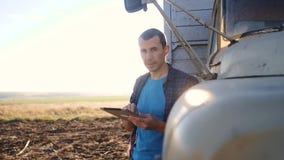 Intelligente Landwirtschaft Mannlandwirtfahrer steht mit einer digitalen Tablette nahe dem LKW Zeitlupevideo Porträtlebensstil stock video