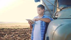 Intelligente Landwirtschaft Mannlandwirtfahrer steht mit Lebensstil eine digitale Tablette nahe dem LKW Zeitlupevideo Porträt stock footage