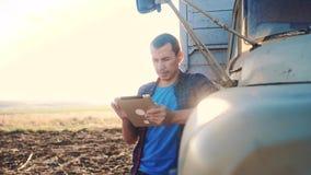Intelligente Landwirtschaft Mannlandwirtfahrer steht mit Lebensstil eine digitale Tablette nahe dem LKW Zeitlupevideo Porträt stock video footage