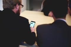 Intelligente mannelijke advocaat in collectieve kleren die aan celtelefoon tijdens vergadering met partners werken Royalty-vrije Stock Fotografie