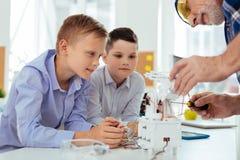Intelligente nette Jungen, die ihren Lehrer betrachten Lizenzfreies Stockfoto