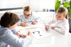 Intelligente nette Kinder schreiben auf Blatt Papier Lizenzfreies Stockfoto