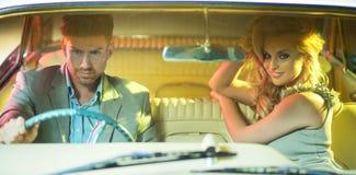 Intelligente Paare, die das Retro- Auto reiten Stockfoto