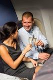 Intelligente Paarreise durch das Flugzeug, das Champagner röstet Stockfotografie