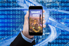 Intelligente Stadt der Geschäftsfrau-Show am intelligenten Handy Stockfotografie