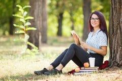 Intelligente Studentendamen-Lesebücher und Entspannung auf einem Parkhintergrund getrennte alte Bücher Kopieren Sie Platz Stockfotografie