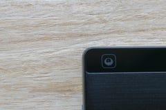 Intelligente Telefonkamera auf hölzernem Hintergrund lizenzfreie stockbilder
