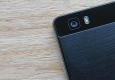 Intelligente Telefonkamera und -blitz auf hölzernem Hintergrund lizenzfreie stockfotografie