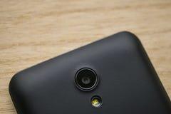 Intelligente Telefonkamera und Blitzholzhintergrund lizenzfreie stockfotografie