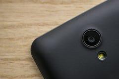 Intelligente Telefonkamera und Blitzholzhintergrund lizenzfreies stockfoto