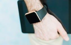 Intelligente Uhr an Hand und Tabletten-PC in der Hand stockbild