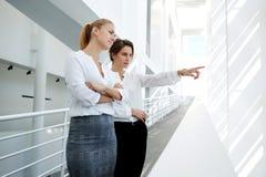 Intelligente vrouwenadvocaat die hun cliënten welke zichtbaar door venster tonen te assoiëren terwijl status in bureaugang, Stock Foto's