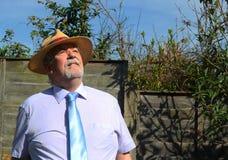 Intelligenter älterer Mann, der einen Strohhut oben schaut trägt Lizenzfreies Stockfoto
