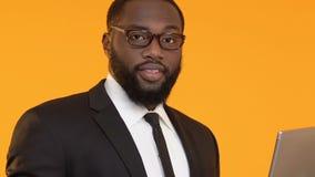 Intelligenter afroer-amerikanisch Mann, der an Laptop arbeitet und die O.K.geste, freiberuflich tätig zeigt stock video