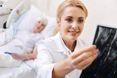 Intelligenter ausgebildeter Doktor, der den Scan ihres älteren Patienten überprüft lizenzfreies stockbild