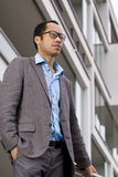 Intelligenter beiläufiger Mann, der außerhalb des Bürohauses denkt Lizenzfreies Stockbild