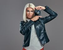 Intelligenter blonder weiblicher Fotograf der Schönheit in einer weißen Bluse und in einer schwarzen Lederjacke, die ein Foto an  Lizenzfreies Stockfoto