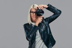 Intelligenter blonder weiblicher Fotograf der Schönheit in einer weißen Bluse und in einer schwarzen Lederjacke, die ein Foto an  Stockfoto
