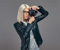 Intelligenter blonder weiblicher Fotograf der Schönheit in einer weißen Bluse und in einer schwarzen Lederjacke, die ein Foto an  Lizenzfreie Stockfotos
