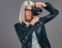 Intelligenter blonder weiblicher Fotograf der Schönheit in einer weißen Bluse und in einer schwarzen Lederjacke, die ein Foto an  Stockfotografie
