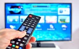 Intelligenter Fernsehapparat und Handpressen Fernsteuerungs Stockfoto