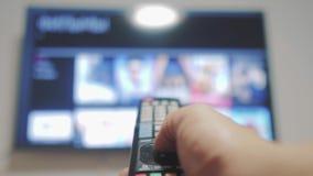 Intelligenter Fernsehlebensstil mit Apps und der Hand Männliche Hand, die weg das intelligente Fernsehen der Fernbedienungsdrehun stock footage