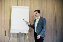 Intelligenter Geschäftsmann, der etwas auf Flip-Chart im modernen Büro darstellt lizenzfreies stockfoto