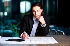 Intelligenter Geschäftsmann, der seine Pläne projektiert Lizenzfreies Stockfoto
