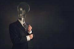 Intelligenter Geschäftsmann mit einer Glühlampe als Kopf lizenzfreie stockbilder