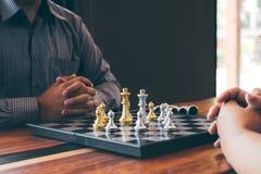 Intelligenter Gesch?ftsmann, der Schachspielwettbewerb mit dem gegen?berliegenden Team, Planungsgesch?ft strategisch zur Entwickl lizenzfreies stockfoto