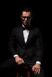 Intelligenter Geschäftsmann in der schwarzen Aufstellung in tragenden Gläsern des dunklen Studios Stockfotografie