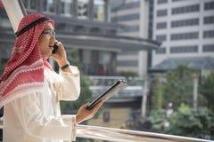 Intelligenter hübscher arabischer Geschäftsmann, der Handy in der Stadt verwendet lizenzfreie stockbilder