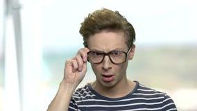 Intelligenter Junge in den Brillen, die eine Idee haben stock video