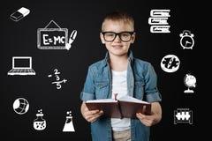 Intelligenter Junge in den Gläsern, die Gläser tragen und ein wichtiges Notizbuch halten Stockbild