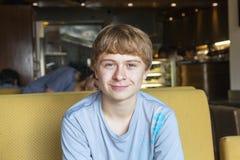 Intelligenter Junge, der in einem Fastfood sitzt Lizenzfreie Stockbilder