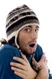 Intelligenter junger Kerl in der Winterschutzkappe, die von der Kälte zittert Stockfotografie