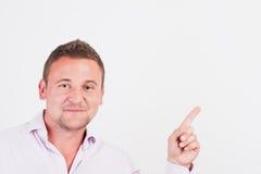 Intelligenter junger lächelnder Mann beim oben zeigen Stockfoto