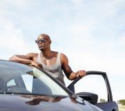 Intelligenter junger Mann mit einem Auto Stockfoto